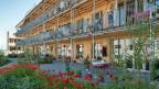 Die Siedlung Oberfeld in Ostermundigen: Vierstöckige Häuser, Holzverkleidungen, viele Balkone - rund 100 Wohnungen.  Es gibt Gemeinschaftsräume, einen grossen gemeinschaftlichen Garten und bald soll noch eine Aussen-Sauna dazu kommen.