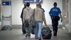 Die Grenzen für Flüchtlinge dicht machen - das wollen rechte Politiker im Tessin. Ein Angehöriger des Grenzwachtkorps führt Migranten zur Zollkontrolle in Chiasso.