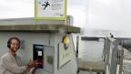 Bevor der Jet d'Eau per Knopfdruck gestartet wird, erfährt SRF-Westschweizkorrespondent Thomas Gutersohn vom Angestellten der Genfer Elektrizitätswerke noch, warum die Wasserfontäne so weiss ist – weil im Zentrum des Wasserstrahls Luft zugeführt wird, die das Wasser gleich nach der Düse zerstäubt.
