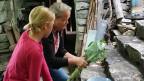 Sanna zeigt einer Besucherin, wie das Gemüse am besten zu rüsten ist. In ihrem früheren Leben hiess Ulricos Ehefrau Sue und lebte mit ihrem damaligen Mann und drei Kindern als Selbstversorgerin auf einer irischen Insel. Später fuhr sie Kohlenschiffe auf der Themse, war Schleusenwärterin und Skipperin. Heute fertigt sie Kunst aus Wolle und packt im Ökodorf mit an.