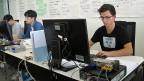 Konzentriert schaut Yannick Burkhart (rechts) auf den Bildschirm, öffnet da ein Fenster, klickt dort auf ein Kästchen. Seine Aufgabe: er soll einem Klassenkollegen einen Fehler im System einbauen.