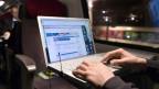 Ab Brig erreicht man Bern dank dem neuen Basistunnel in einer Stunde und drei Minuten. Bild: «Laptop-Nomade» beim Surfen im Zug.