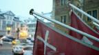 Die Kantonsflagge des Kantons Schwyz hängt vor dem Schwyzer Rathaus an einem Balkon.