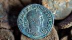 Eigentlich war es ein Maulwurf, der den Schatz ausgebuddelt hat. Der Landwirt entdeckte die grün schimmernden Münzen nämlich auf einem Maulwurfshügel. Bild: Römische Münze aus dem 3. Jahrhundert, gefunden 2014 im Tessin.