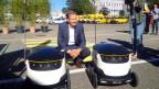 Dieter Bambauer, Leiter PostLogistics, demonstriert in Bern eine Paket-Lieferung mit zwei Robotern.