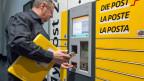 Ein Mitarbeiter der Post bedient einen «My Post Automaten» des Post-Netzes der Zukunft.