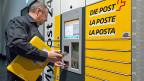 Ein Post-Mitarbeiter bedient einen «My Post Automaten». Längst nicht allen Postkunden gefällt der Service-Abbau der Post.