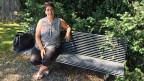 Die neue MCG-Präsidentin Ana Roch sitzt auf einer Bank im Park hinter dem Rathaus von Vernier, der grössten Genfer Gemeinde.