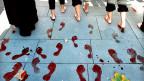 14'000 Mal jedes Jahr wird in der Schweiz wegen häuslicher Gewalt die Polizei gerufen. Bild: Eine Aktion gegen häusliche Gewalt im spanischen Sevilla: Frauen hinterlassen auf einem Platz blutrote Fussabdrücke.