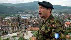 Ein Swisscoy-Soldat steht auf einer Anhöhe über der Stadt Mitrovica.