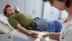 Eine Hausärztin versorgt einen verletzten Patienten.