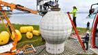 Mitarbeiter des Fraunhofer-Instituts bereiten in Konstanz am Ufer des Bodensees einen Kugelspeicher aus Beton vor, um diesen zu Testzwecken zu versenken.