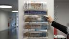 Eine Person nimmt einen Stellenanzeiger aus einem Zeitungshalter im Regionalen Arbeitsvermittlungszentrum RAV in Bern.