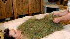 Ein Hotelgast lässt sich von einem Wellnessexperten mit Bio-Heu der hiesigen Bergweiden bedecken, was den Kreislauf anregen soll.