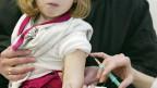 Eine Ärztin impft ein zweijähriges Mädchen gegen Masern.