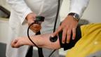 Ein Arzt misst bei einer Patientin den Blutrdruck.