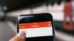 Ein Smartphone mit der Mobile Ticketing App lezzgo, im Hintergrund ein Personenzug der SBB.