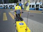 Ein Velo-Fahrer von hinten mit einem gelben TCS-Anhänger.