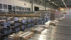 In der riesigen Werkhalle von Alu-Laufen stapeln sich bereits meterhoch Alu-Rundstangen. Bild: Charlotte Jaquemart.