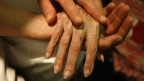 Eine jüngere Hand hält eine ältere Hand.