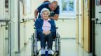 Junger Mann kümmert sich um eine Rollstuhlfahrerin.