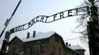 Das Bild zeigt das Eingangstor zum Konzentrationslager Auschwitz mit der Überschrift «Arbeit macht frei».