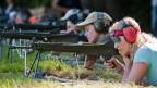 Schützinnen und Schützen in einem Schiessstand.