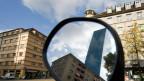 Ein Mehrfamilienhaus und der Messeturm spiegeln sich in einem Rückspiegel eines Autos. Symbolbild.