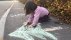 Spielendes Kind auf einer Quartierstrasse.