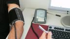 Einem Mann wird der Blutdruck gemessen.