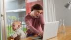 Eine Mutter am Laptop mit Telefon. Neben ihr sitzt ihr Kind im Kinderstuhl.