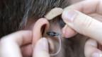 Eine Person wird ein Hörgerät angepasst.