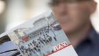 Ein Mann schaut in eine Broschüre des RAV.
