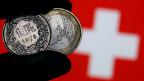 Symbolbild. Schweizer Franken und Euro vor einer Schweizer Fahne.