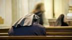 Betende Nonne in einer Kirche. Symbolbild.