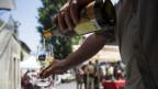 Ein Mann schenkt auf einem belebten Gässchen ein Glas Weisswein ein.