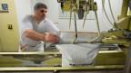 Ein Arbeiter füllt in der Fabrik der Firma Hochdorf Milchpulver in einen Sack.