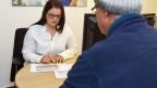 Sozialarbeiterin berät einen Klienten. Symbolbild.