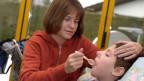 Symbolbild. Eine Frau betreut ein krankes Kind zu Hause.