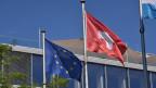 Die Schweizer Fahne und die EU-Fahne.