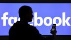 Die Silhouette eines Mannes vor dem Facebook-Schriftzug.