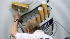 Symbolbild. Ein Plakat mit Tabakwerbung wird aufgehängt.