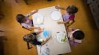 Auf dem Bild sind Kindergärtner im Tessin zu sehen, die über Mittag in der Mensa essen.