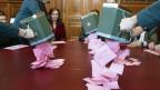 Weibel leeren bei den Stimmenzählern und -zählerinnen die Urnen mit den Wahlzetteln aus.