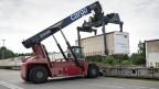 Mit einem fahrbaren Kran werden Container von LKWs auf die Schiene verladen.