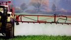 Symbolbild. Ein Traktor verspritzt auf einem Feld Pestizide.