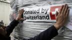 Ein Mitarbeiter des DEZA verlädt Hilfsgüter für Flüchtlinge und Migranten. Symbolbild.