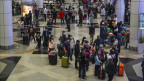 Symbolbild. Viele Menschen auf einem Flughafen tragen zur Sicherheit Mundschutz-Masken.