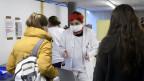 Menschen melden sich bei einer Ärtin in der Notfallstation eines Spitals.