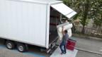 Ein Mann lädt Mobiliar in einen Zügelwagen.